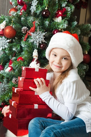 Little girl in Santa hat with gifts near christmas tree