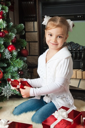 Happy little girl open a red gift box