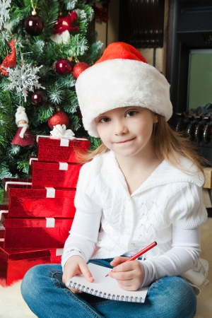 Little girl in Santa hat writes letter to Santa near christmas tree photo