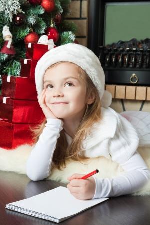 漂亮的女孩在聖誕老人的帽子寫一封信給聖誕老人附近聖誕樹 版權商用圖片
