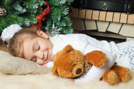 Little girl sleeping with teddy bear near christmas tree
