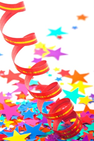 Streamer and multicolored confetti stars on the white background photo