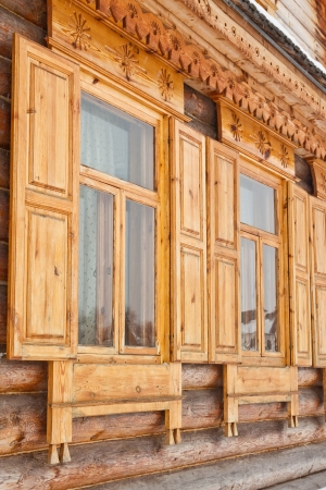 Two carved windows of old wooden house