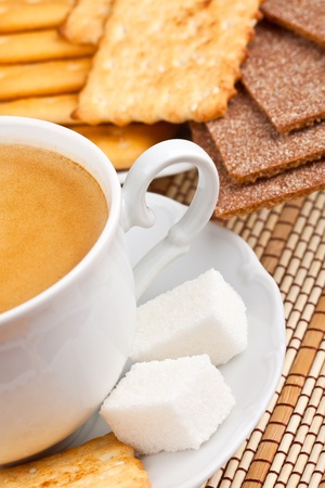 A cup of  coffee with a lump sugar and crackers for breakfast