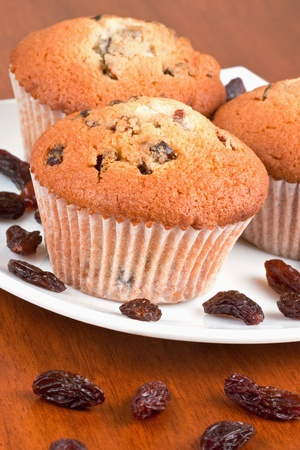 raisins: Three muffins on a white plate on the table Stock Photo