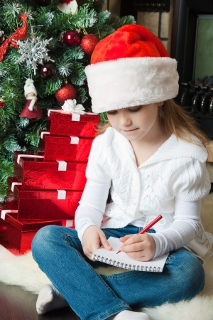Girl in Santa hat writes letter to Santa near christmas tree photo