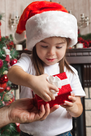 three palm trees: Christmas gift from father for little girl in Santa hat