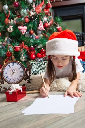 Funny girl in Santa hat writes letter to Santa near christmas tree and clock photo