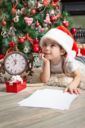 Little girl dreams about the gift and writes letter to Santa near christmas tree Stok Fotoğraf