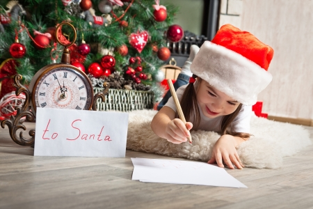 Happy girl in Santa hat writes letter to Santa Claus near christmas tree and clock