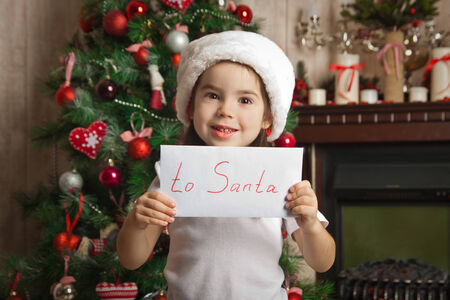 Little girl with letter to Santa near christmas tree photo
