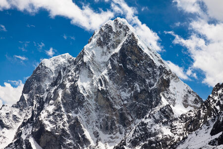 Himalayan mountains Cholatse and Tabuche Peak at the blue sky with clouds on a sunny day photo