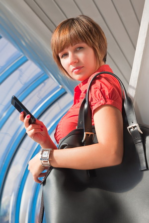 large woman: Girl in a red blouse with a black bag and phone