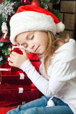 Pretty girl in Santa hat sleeping on the gifts near christmas tree