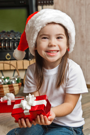 three palm trees: Smiling little girl in Santa hat with red gift box for Christmas Stock Photo