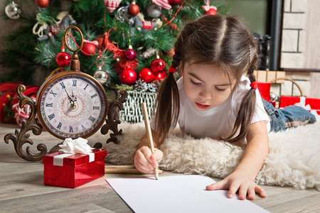 Girl in Santa hat writes letter to Santa Claus near christmas tree and clock