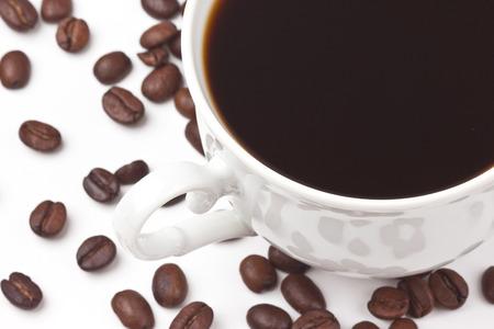 tarde de cafe: Una taza de café en el café de fondo frijol