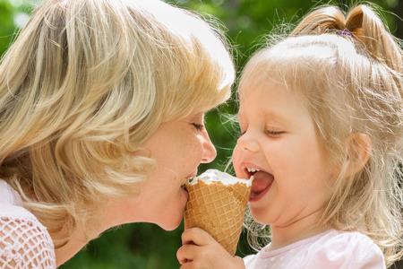 botanas: Madre feliz y pequeña hija comiendo helado en día de verano