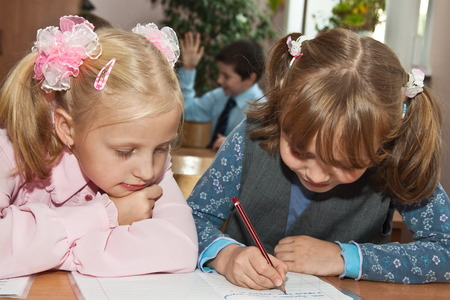 Elementary school. Girl writing in a notebook, and a friend carefully watching Stock Photo