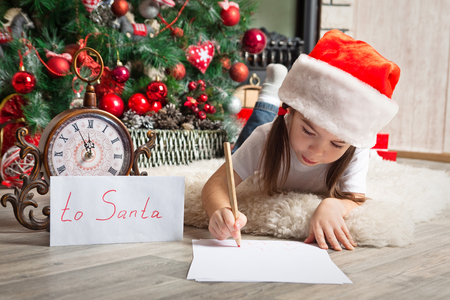Little girl in Santa hat writes letter to Santa Claus near christmas tree and clock Stock Photo