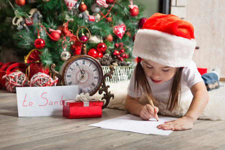 Little girl in Santa hat writes letter to Santa Claus near christmas tree Stock Photo
