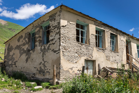 Destroyed stone house with broken windows Stock Photo