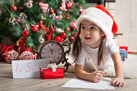 sobres para carta: Niña pensativa en el sombrero de Santa escribe carta a Santa Claus cerca del árbol de navidad Foto de archivo