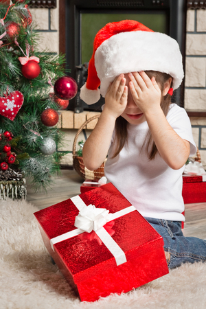 Little girl with  closed eyes in Santa hat with Christmas gift Stock Photo