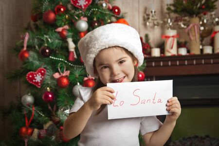 Happy little girl in christmas hat holding letter for Santa