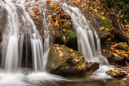 Beautiful waterfall in the autumn forest with fallen leaves