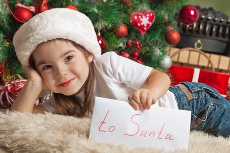 Happy little girl with letter to Santa near christmas tree Stock Photo