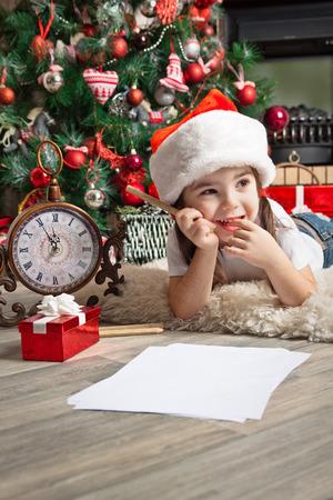 persona escribiendo: Ni�a pensativa en el sombrero de Santa escribe carta a Santa Claus cerca del �rbol de navidad Foto de archivo