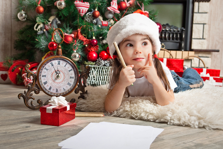 Little girl dreams about the gift and writes letter to Santa near christmas tree Stock Photo