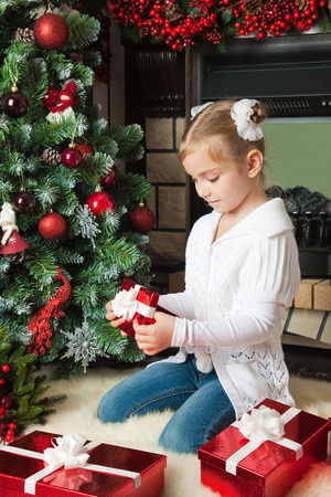 Little girl open a red gift box near christmas tree