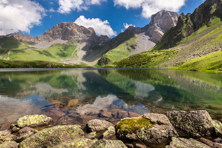 lofty: Panoramic view of the idyllic summer landscape with mountain lake and a high rock in the background Stock Photo