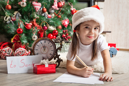 3 4 years: Little girl in Santa hat writes letter to Santa Claus near christmas tree Stock Photo