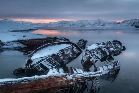 Old sunken fishing boats on the shore of the Barents Sea at sunrise. Teriberka. Russia