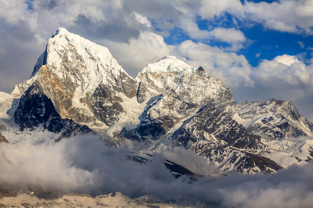Himalayan mountain tops in beautiful clouds in sunlight at sunset. Nepal
