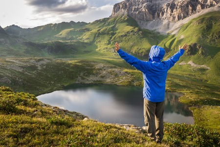 Man traveler with raised hands standing on a hill above a mountain lake and enjoy the sunset. Concept of extreme sport and active life Stock Photo