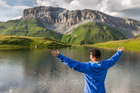 Hiker standing with raised hands near the beautiful mountain lake and enjoying view. Concept of extreme sport and active life Stock Photo