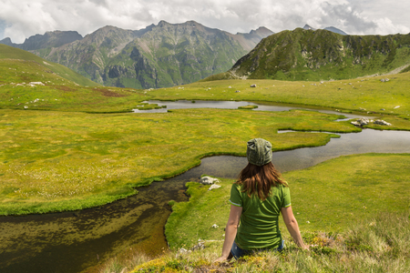 Back view hiker woman sitting on hill and looking at sunny river valley. Adventure, travel, tourism and hike concept