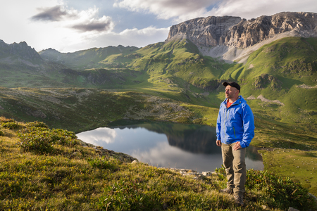 Hiker relaxing and enjoying beautiful summer mountain landscape. Adventure concept lifestyle