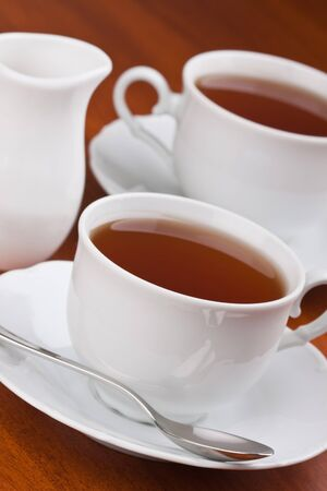 Black tea in cups with saucers on the table