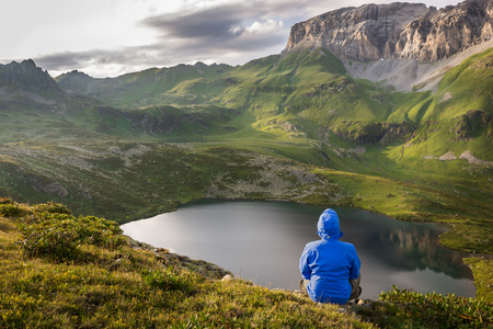 Man relaxing and enjoying beautiful summer mountain landscape during his hiking trip. Travel concept lifestyle Stock Photo