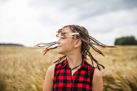 Attractive teenage model girl with fluttering braids in the field with wheat
