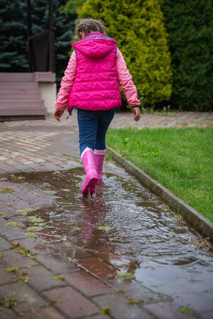 Little girl in pink vest and rubber boots walking in a puddle after rain in autumn. Having fun outdoors Stok Fotoğraf