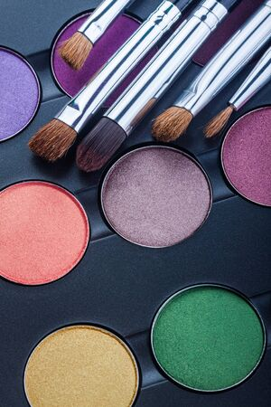 Multicolor shades of professional colorful eyeshadow palette and brushes. Eye makeup