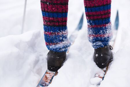 Female legs in multicolored knitted socks stand on a vintage wooden ski
