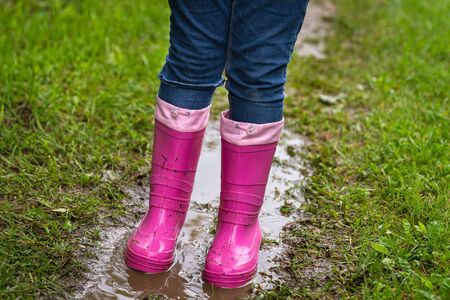 Girl wearing rubber boots standing in a dirty puddle on a summer day. Outdoors concept Stok Fotoğraf