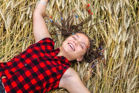 Smiling girl with braids in a blouse lying on ears of wheat on a summer day. Outdoors concept Stok Fotoğraf